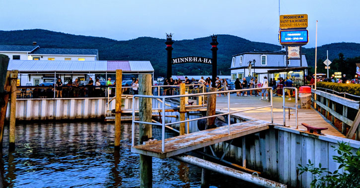 a dock in Lake George with a Minne Ha Ha sign and people