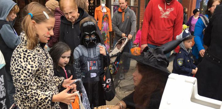 costumed kids on the street getting candy from a witch