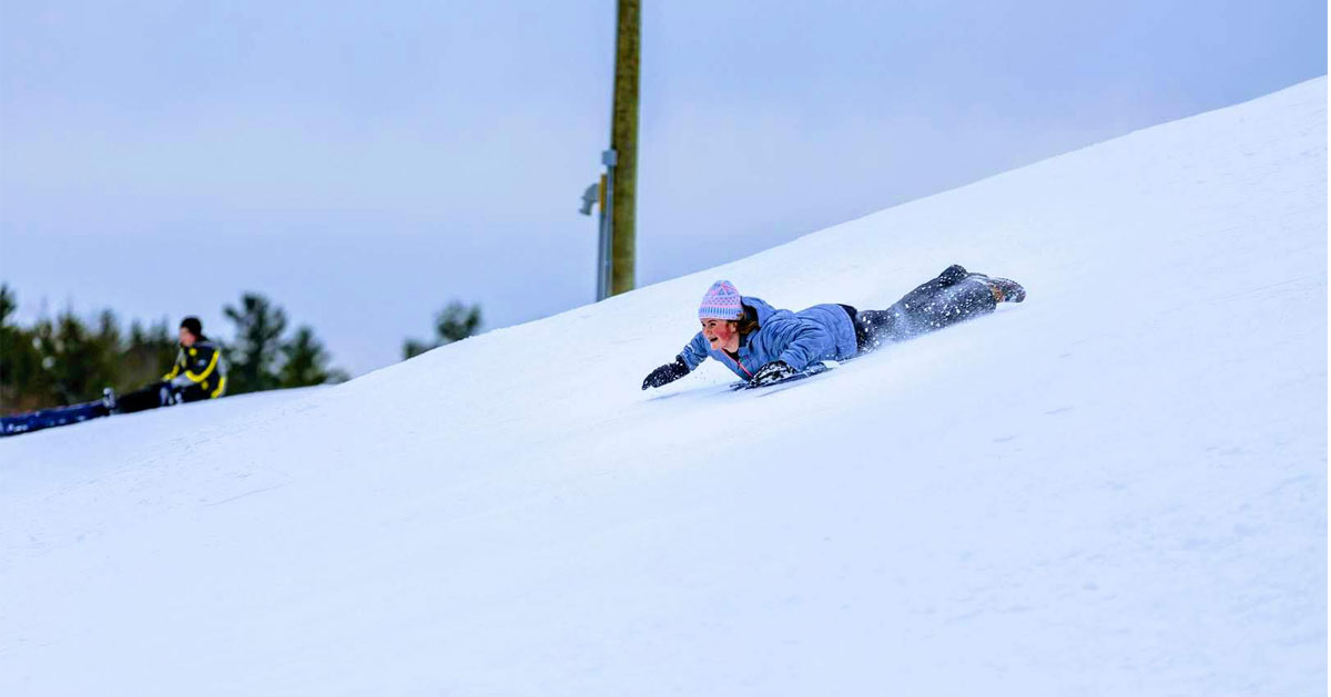 girl sleds down a hill