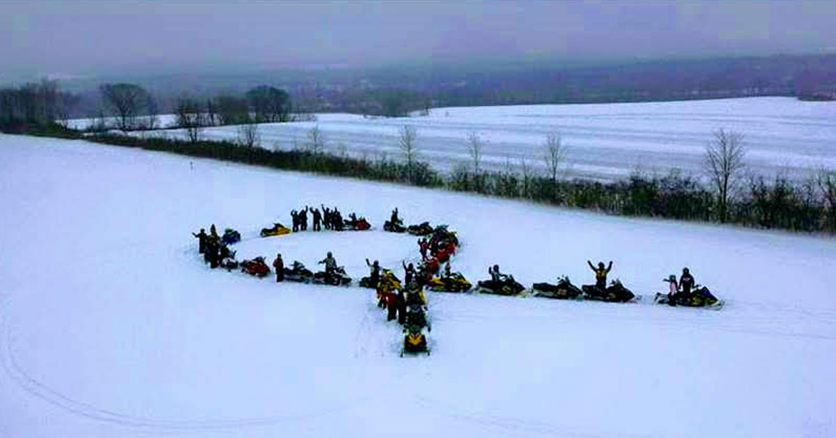 snowmobilers in the formation of a cancer ribbon