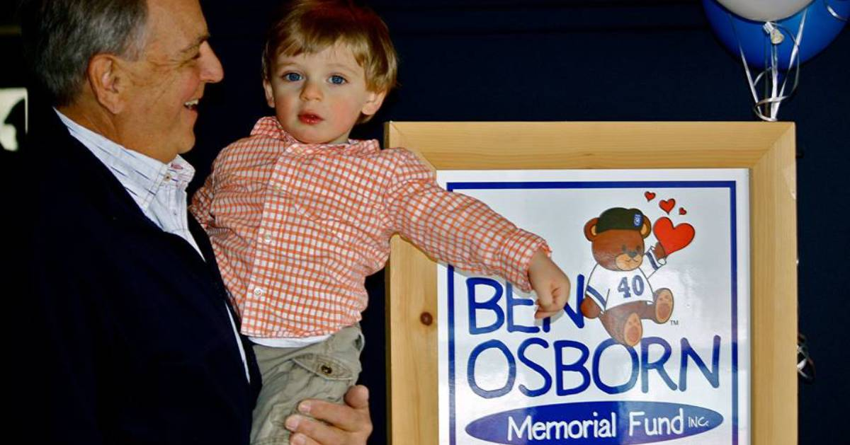 man with kid in front of Ben Osborn Memorial Fund sign