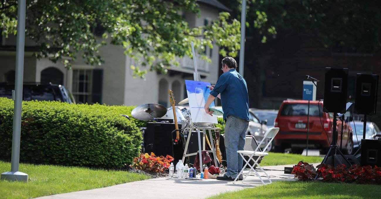a man paints at his easel on a sidewalk