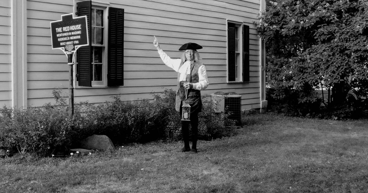 black and white photo of a Benjamin Franklin next to a house