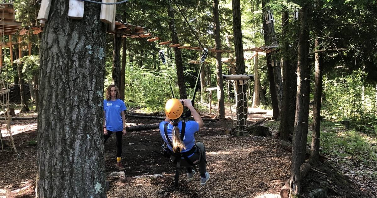 person ziplining in woods adventure course