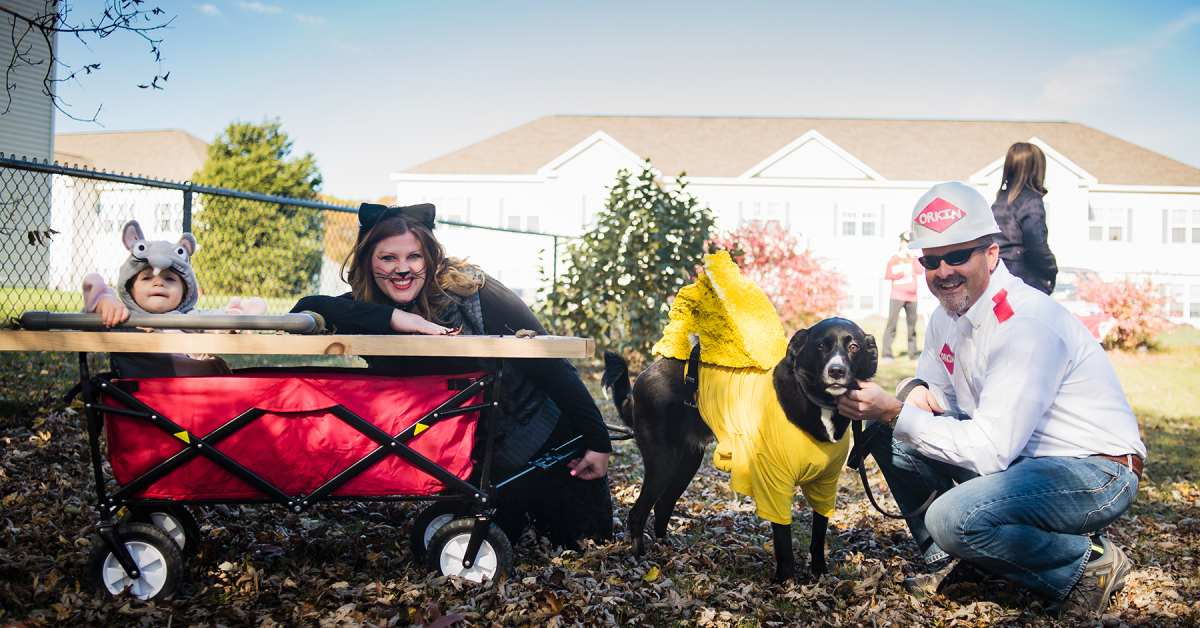 a family dressed up in a group costume with their dog