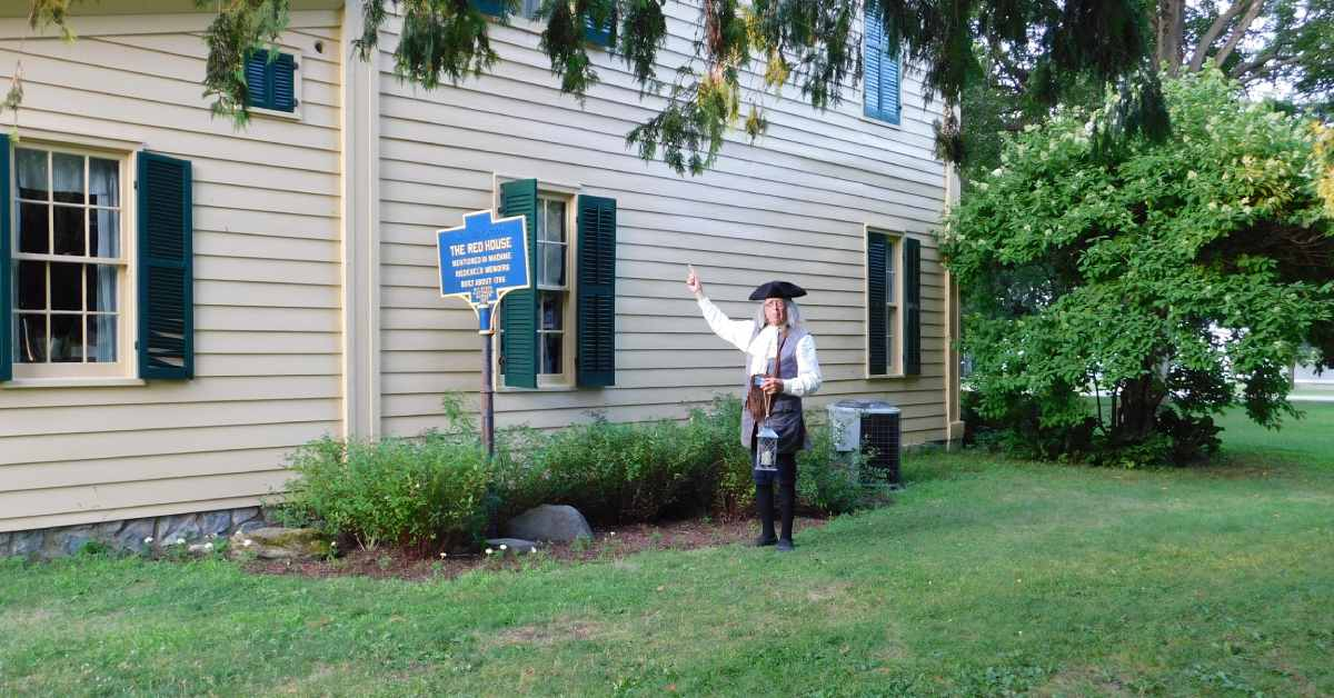 a ben franklin reenactor outside the old fort house