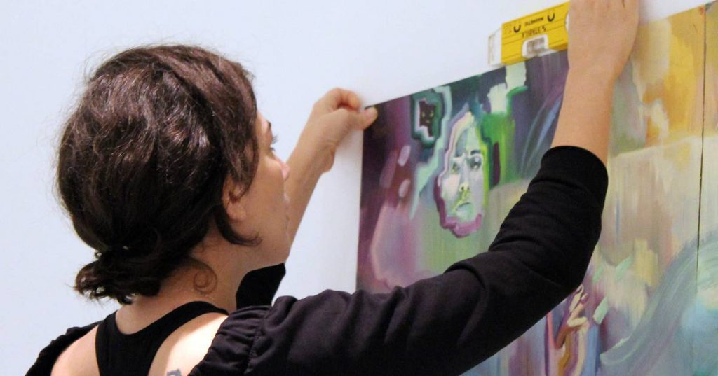 woman hanging painting on gallery wall