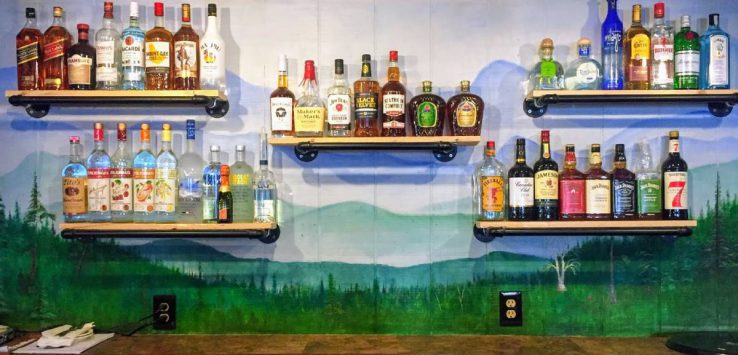 back of bar with mural and liquor bottles