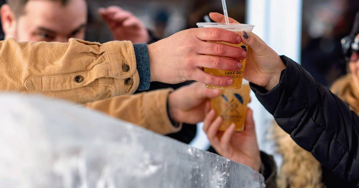 hands reaching for ice bar drink