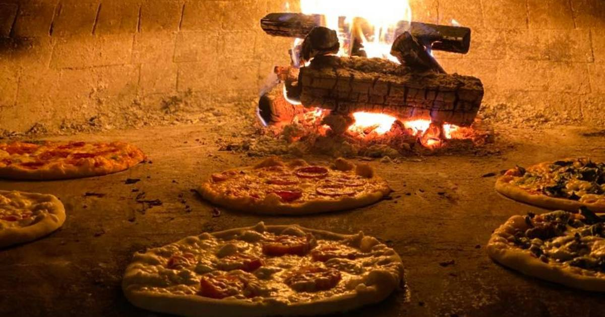 pizza being cooked in wood fired oven