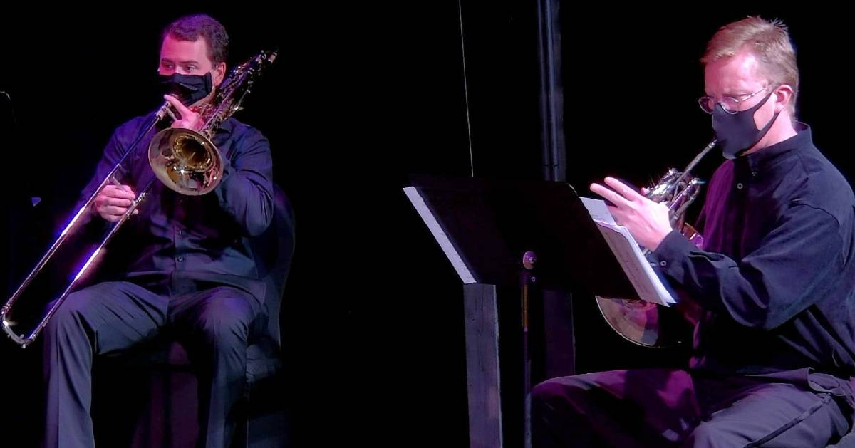 two symphony performers wearing masks