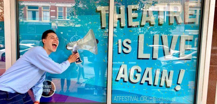 theatre is live again in a window, man stands in front of it